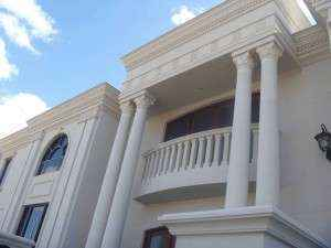 White Roman style pillars in fromt of two story house.